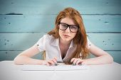 Pretty redhead typing on keyboard against painted blue wooden planks