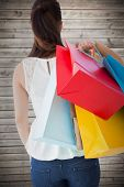 Rear view of brown hair holding shopping bags against wooden planks background