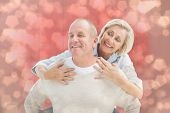 Happy mature man giving piggy back to partner against light glowing dots design pattern