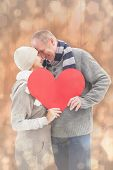 Happy mature couple in winter clothes holding red heart against light glowing dots design pattern