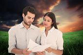 Attractive young couple reading their bills against green field under orange sky