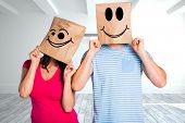 Young couple with bags over heads against screen in modern white room