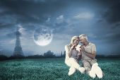 Happy couple sitting and holding present against bright moon over paris