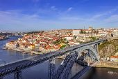 View of the iconic Dom Luis I bridge crossing the Douro River, and the historical Ribeira and Se District in the city of Porto, Portugal. Unesco World Heritage Site.
