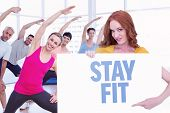 Pretty redhead showing a poster against stay fit