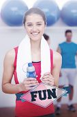 The word fun and female holding water bottle with fitness class in background against badge