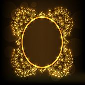 Beautiful floral design decorated golden frame in oval shape on brown background.