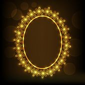 Shiny floral design decorated golden frame in oval shape on brown background.