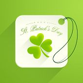 Beautiful tag or label with glossy shamrock leaf on green background for Happy St. Patrick's Day celebration.