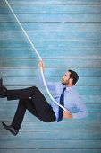 Businessman pulling a rope with effort against wooden planks