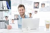 Handsome man working at his desk on laptop smiling at camera against profile pictures
