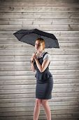Pretty redhead businesswoman holding umbrella against wooden planks background