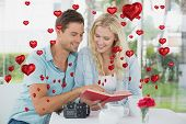 Cute hipster couple reading book together at table against red heart balloons floating
