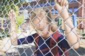 A sad little girl at school playground