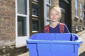 A Young girl with recycle bin outside