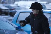 picture of scrape  - Mature woman in a coat scraping windows in the winter time - JPG