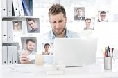 Happy man working at his desk on laptop against profile pictures