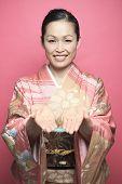 A Beautiful japanese kimono woman in pink background