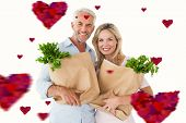 Happy couple carrying paper grocery bags against hearts