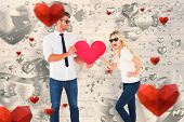 Cool young couple holding red heart against grey valentines heart pattern