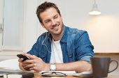 Portrait of young businessman listening music with mobile phone at office