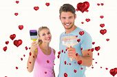 Young couple smiling and holding paintbrushes against red heart balloons floating