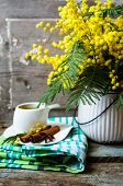 foto of mimosa  - Glass cup with tea and blooming yellow mimosa with good morning note on wooden background - JPG