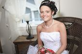 A bride in wedding dress posing at home and waiting for groom. R
