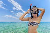 stock photo of sky diving  - Beautiful teen girl prepares diving mask against endless sea infinite horizon blue green sea super clean waters and blue skies separated by a far away horizon - JPG