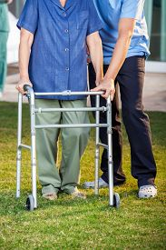 picture of zimmer frame  - Low section of male caretaker helping senior woman in using walking frame at nursing home lawn - JPG