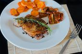 pic of roasted pork  - Pork steak with roasted carrots and dried tomatoes on white plate - JPG