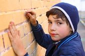foto of graffiti  - preteen handsome boy try himself as a graffiti artist on the yellow brick wall