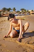 stock photo of preteen  - preteen handsome boy play with sand on the red sea beach and yaht background - JPG