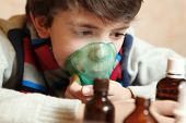 foto of inhalant  - boy with electric inhaler as a curation against virul disease flue