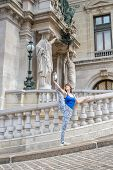 stock photo of legs air  - Ballerina on holiday casually dressed making a pose with her leg high up in the air in front of Paris National Opera House - JPG