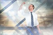 foto of clenched fist  - Businessman cheering with clenched fist against window overlooking city - JPG