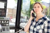 pic of phone-booth  - young woman making a phone call at a public phone box - JPG
