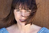 pic of blow-up  - Close up portrait of a mature woman with hair blowing in wind  - JPG