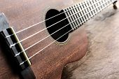 picture of ukulele  - Close up of ukulele on old wood background with soft light Vintage tone - JPG