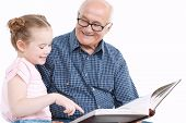 stock photo of granddaughters  - Portrait of a grandfather wearing blue checkered shirt looking at his small pretty granddaughter sitting next to him pointing into the big brown book and smiling - JPG