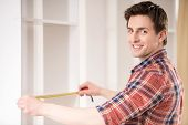 picture of measurement  - Young man measuring home furniture with measure tape - JPG