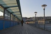 stock photo of walking away  - A guy in his army suit walking away from the camera walking at the pier at sunset hour on a summer day with no clouds in the sky - JPG