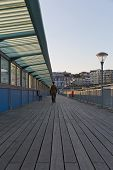 picture of walking away  - A guy in his army suit walking away from the camera walking at the pier at sunset hour on a summer day with no clouds in the sky - JPG
