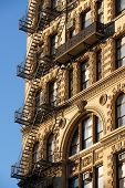 picture of wrought iron  - Fire escape and ornamented facade with wrought iron balcony on brick building in Chelsea Manhattan New York City - JPG