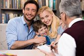stock photo of psychologist  - Cheerful family of three talking with psychologist - JPG