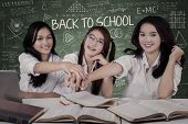 picture of joining hands  - Attractive female high school students joining hands together in the classroom - JPG