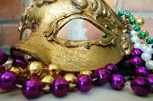 picture of masquerade  - A gold Mardi gras masquerade mask and beads - JPG