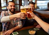people, men, leisure, friendship and celebration concept - happy male friends drinking beer and clin poster