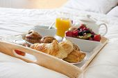 stock photo of bed breakfast  - breakfast in bed with fruits and pastries on a tray - JPG