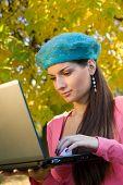 Teenager using laptop outdoors